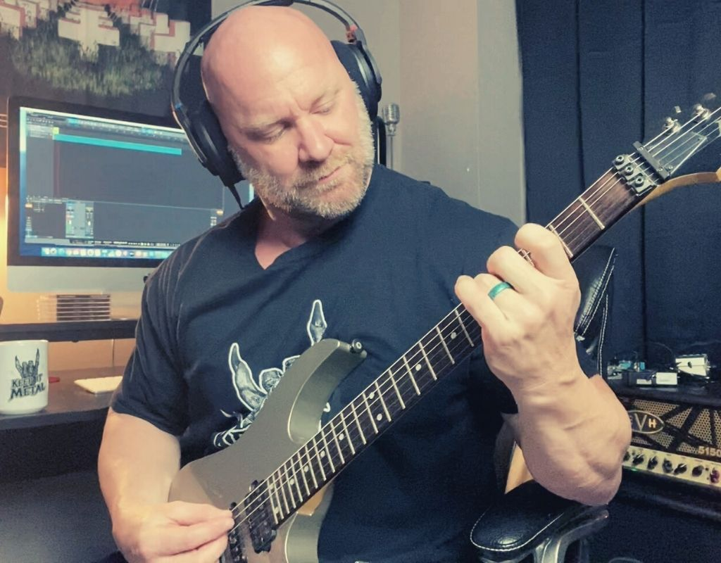 playing Ibanez guitar in the studio recording